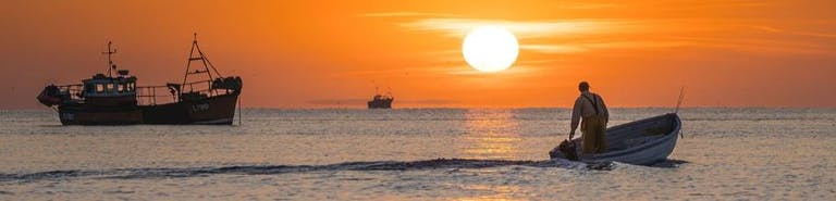 Fishermen heading out for a catch to the backdrop of an orange sunrise, Selsey