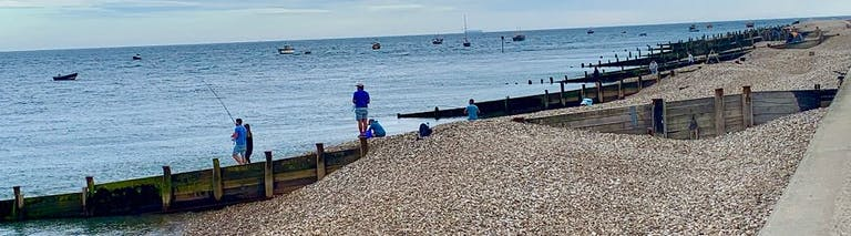 People gather to fish off of East Beach, Selsey