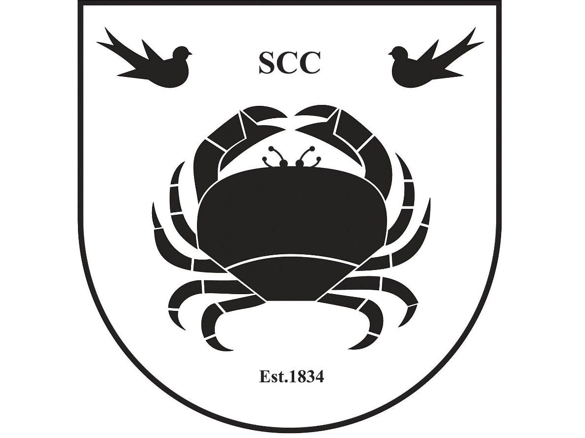 Selsey Cricket Club Logo comprising of a shield featuring one central large crab and two small birds.