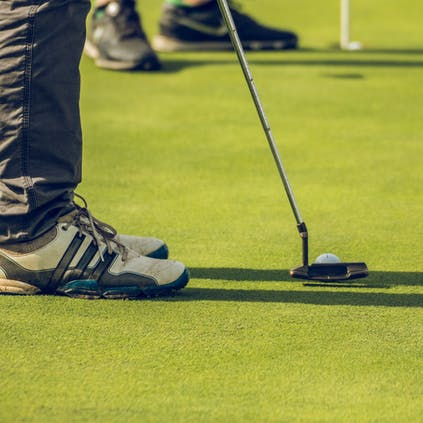The lower legs and trainers of an individual lining up their putter with the ball