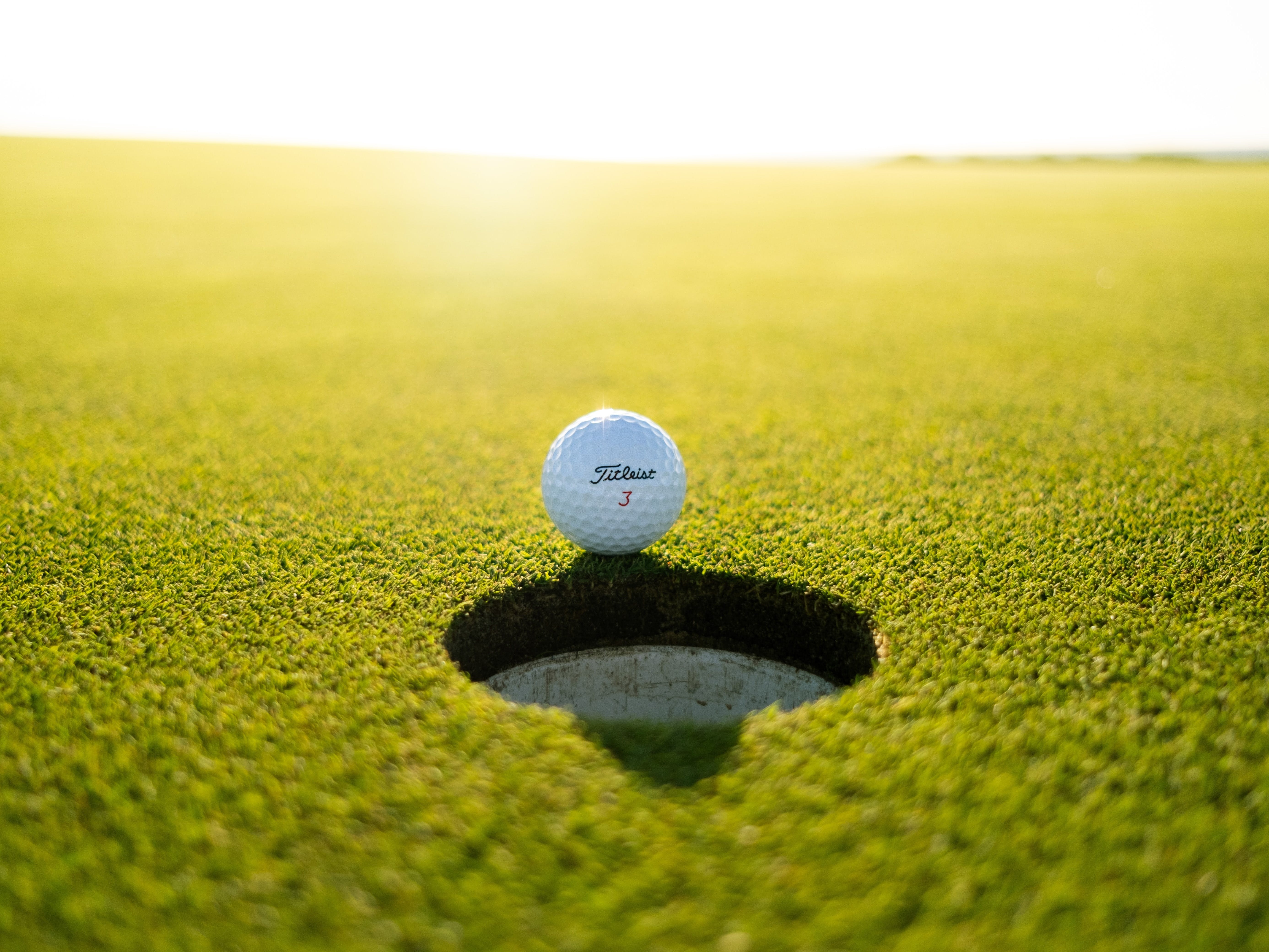 A golf ball teeters on the edge of a hole