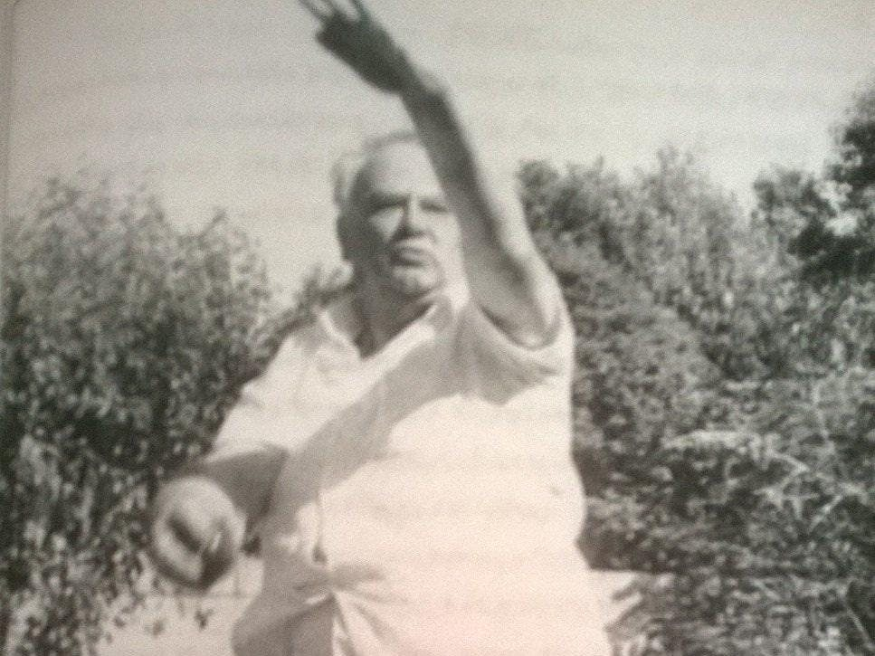 A black and white image of Sir Patrick Moore wearing cricket whites and in mid bowl action