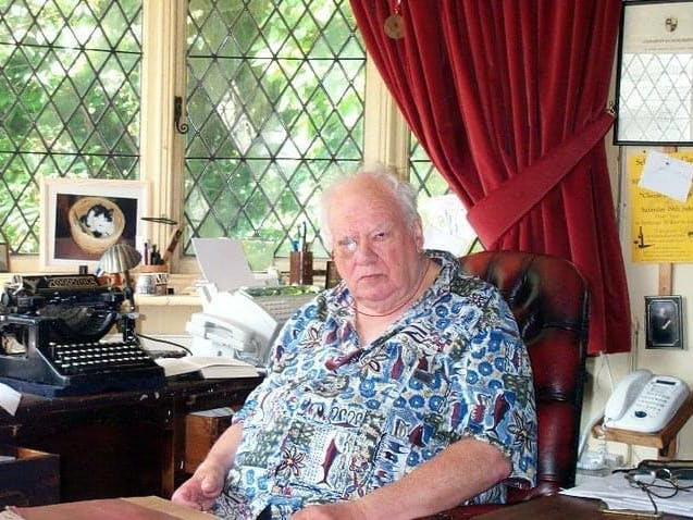 Sir Patrick Moore sat at a busy desk which incudes an old typewriter