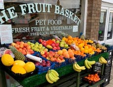 Front of the Fruit Basket Shop with fresh fruit laid out consisting of bannanas, melons, apples, oranges and pinapples