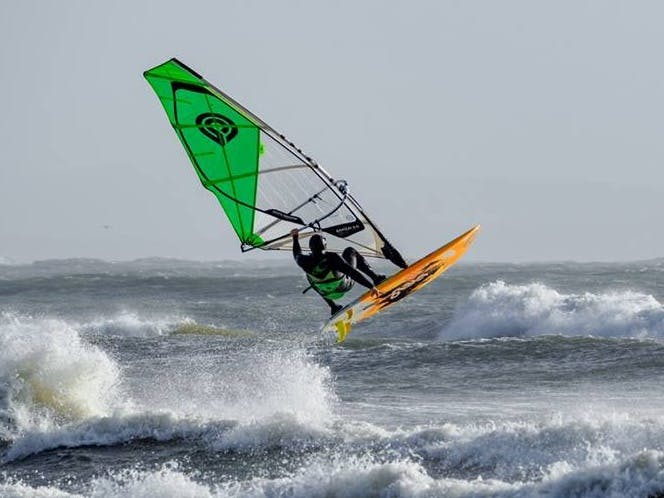 Windsurfer out in the waves on an orange board with green sail.