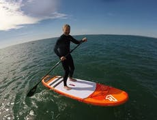 Paddle boarder on an orange and white board, standing upright on it on the sea waters