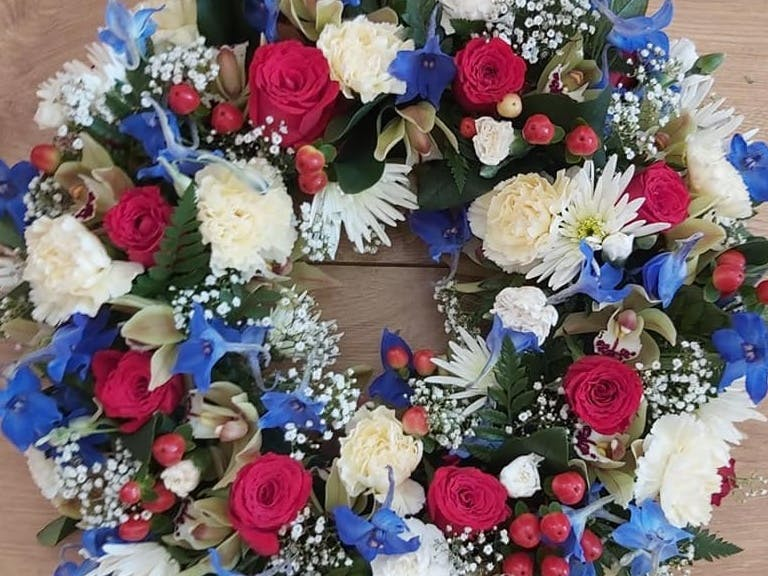 Ring of flowers consisting of reds, blues and whites