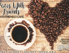 Advertisement for Paws with Friends  showing coffee beans in a heart shape and a cup of coffee on a stripped wooden table
