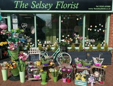 The Selsey Florist with frontage display made up of the shop window, a ladies bicycle surrounded by pots and vases of flowers and balloons.