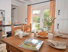 An image of Sea Pinks Cottage in Selsey, the kitchen with dressed table ready for breakfast with fresh croisants with the natural light flooding through the kitch window over looking the lush garden.