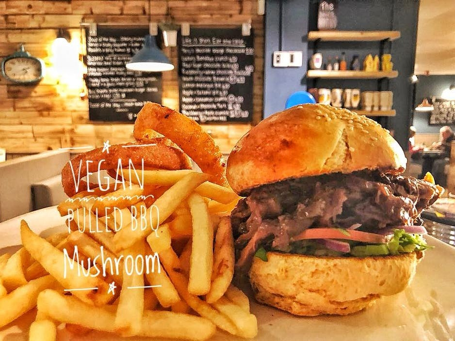 Delicious looking vegan pulled BBQ Mushroom burger with lashings of fries set in the restaurant of The Riviera