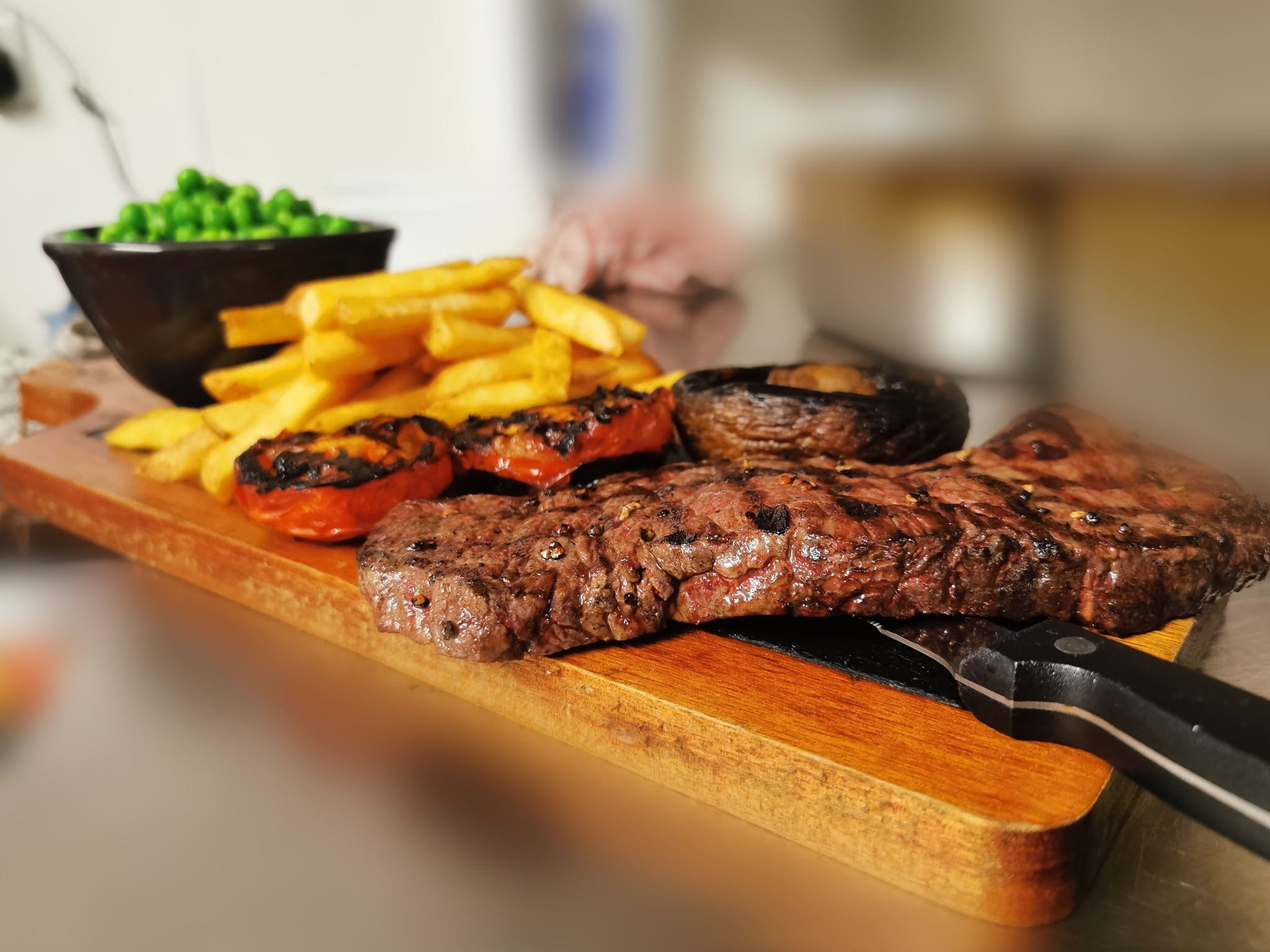 A platter of grilled steak, grilled tomatoes, mushroom, chips and peas served at The Crown Inn
