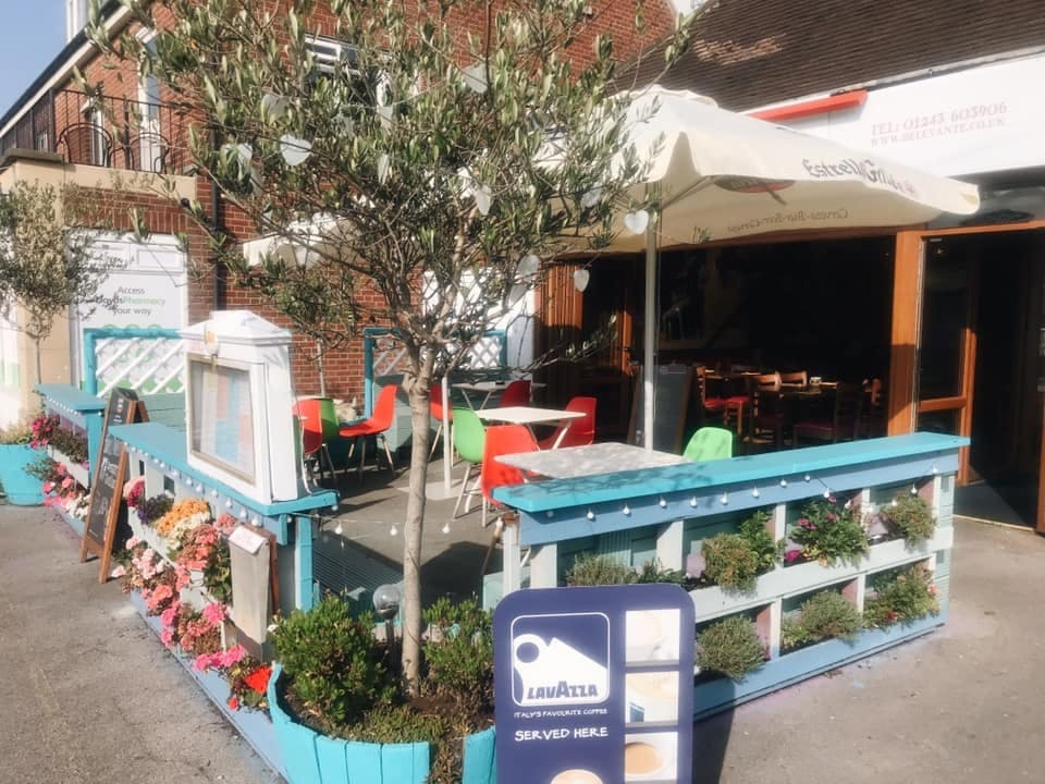 The outside space of the restaurant Viento De Levante including seating area with parasol and olive trees in bright blue tubs.