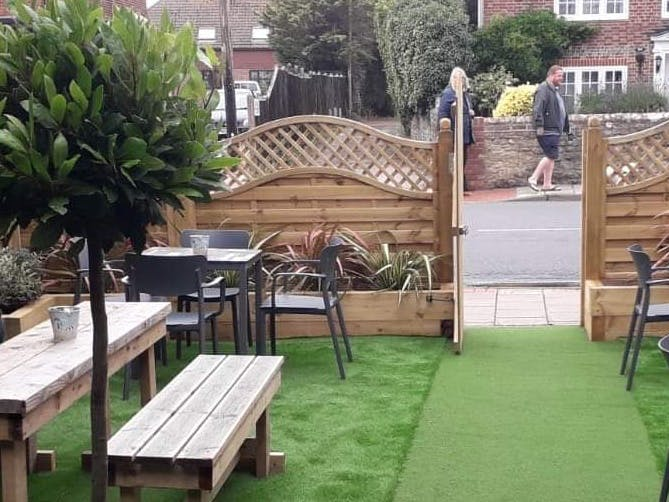 Image of the enclosed beer garden at the Crab Pot pub in Selsey with seating and planting.