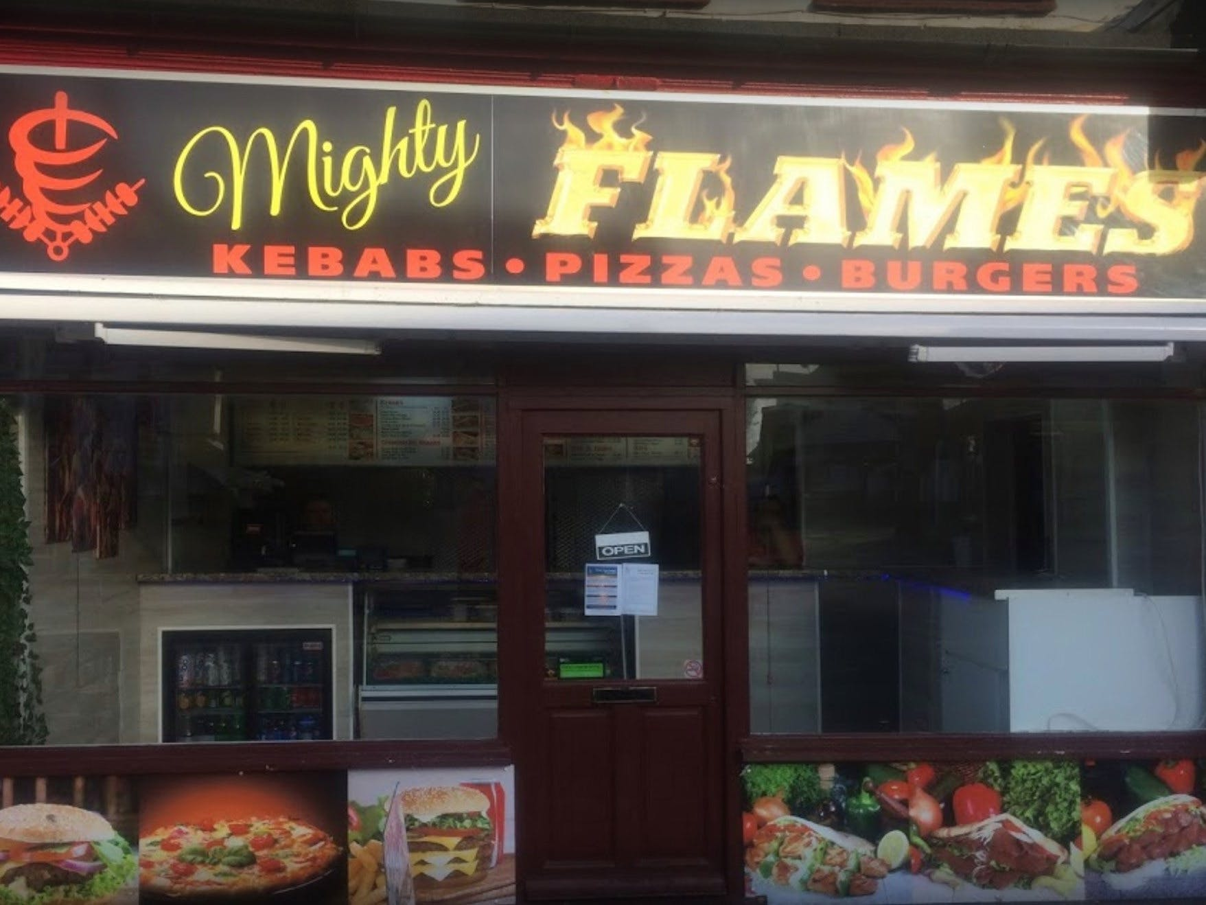 The shop front of Mighty Flames takaway, advertising its kebabs, pizzas and burgers.