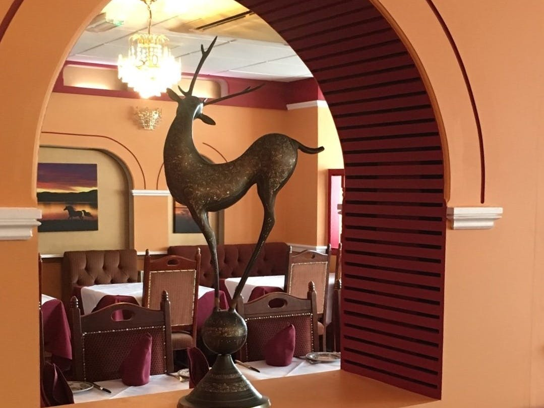 A view of the dining area at the New Magna Tandoori Restaurant looking through an arch with a deer scultpture in the foreground