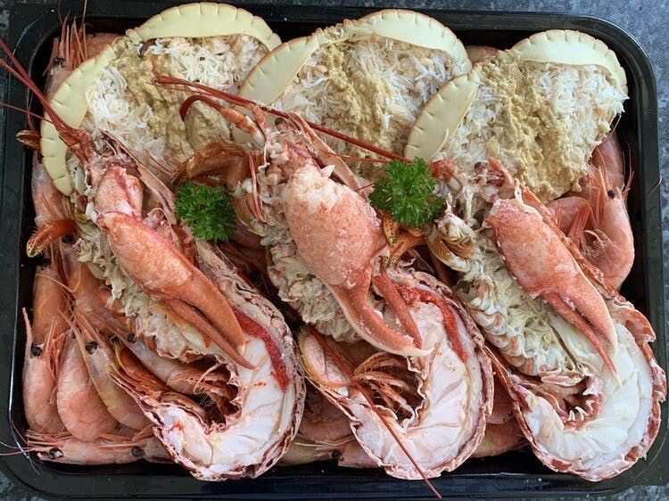 A platter of 3 dressed crabs, three half lobsters and prawns in their shells