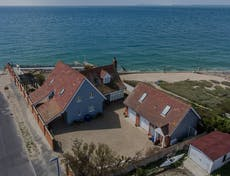 Aeria view of the beach house and its out buildings right by the open sea