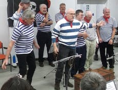 The Selsey Shantymen performing dressed in their blue and white striped shirts and red scarfs
