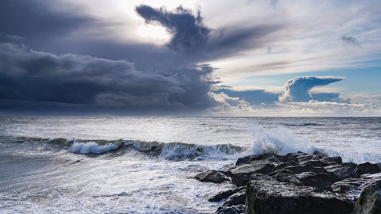 The waves hitting rocks and the clouds take on a majestic formation in the sky