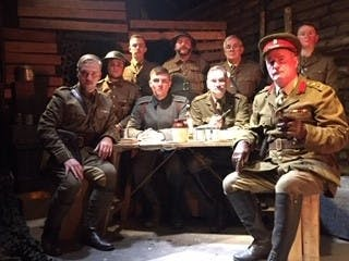 Image of 9 actors dressed in World War 1 uniforms acting out a scene from Journey's End