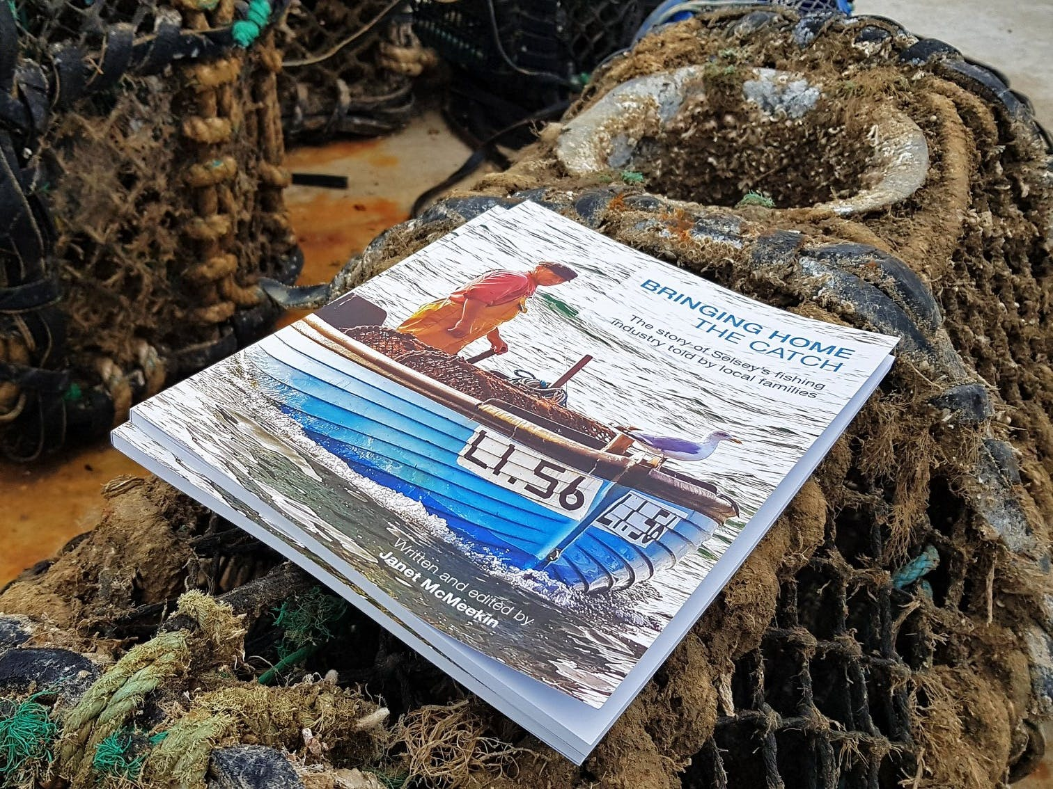 Image of the Bringing Home the Catch publication placed on a prawn pot