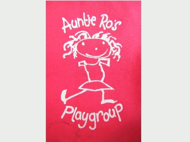 Auntie Ro's Playgroup logo made up of a red background with an artistic white outline of smiley child with the words Auntie Ro's Playgroup
