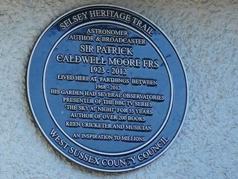 Image of the blu plaque placed on Sir Patrick Moore's home in Chichester. Wording reads, Astronomer, Author and Broadcaster Sir Patrick Caldwell Moore FRS 1923 - 2012 lived here at Farthings between  1968 - 2012. HIs garden had several observatories. Presenter of the BBC TV series 'The Sky At Night' for 55 years. Author of over 200 books. Keen cricketer and musician. An inspiration to millions.
