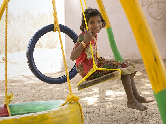 Young girl smiling on swing