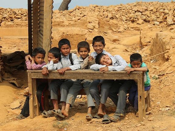 Schoolkinderen aan tafel in de ruines van school