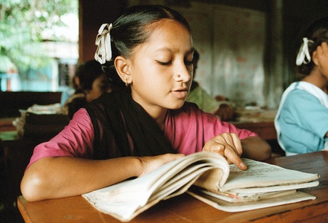Girl reading a book in class