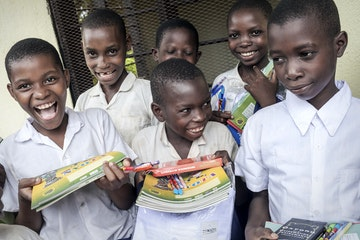 Children holding their schoolbooks and smiling