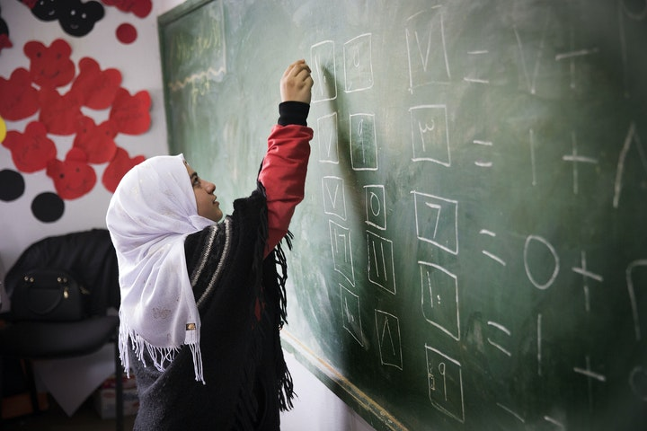 Girl in schoolclass writing on board