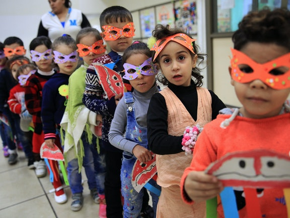 Children standing in line in school, wearing a mask