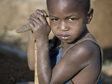Small child with axe in the gold mines of Tanzania