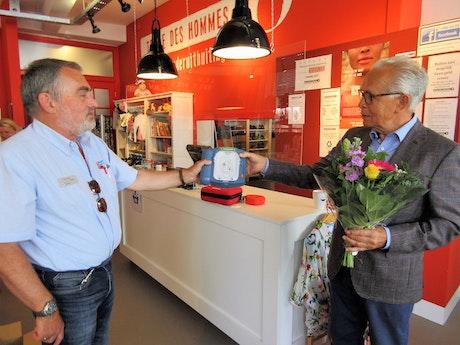 overhandigen van de AED met links op de foto Hans Smits , schipper waterlijn en recht Hans Gelauff ,voorzitter Terre des Hommes Amersfoort
