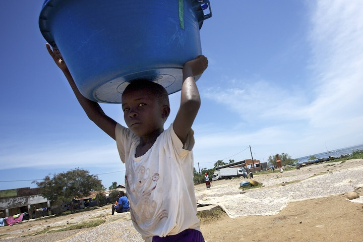 Child carrying fish on the shores of Lake Victoria, Kenya