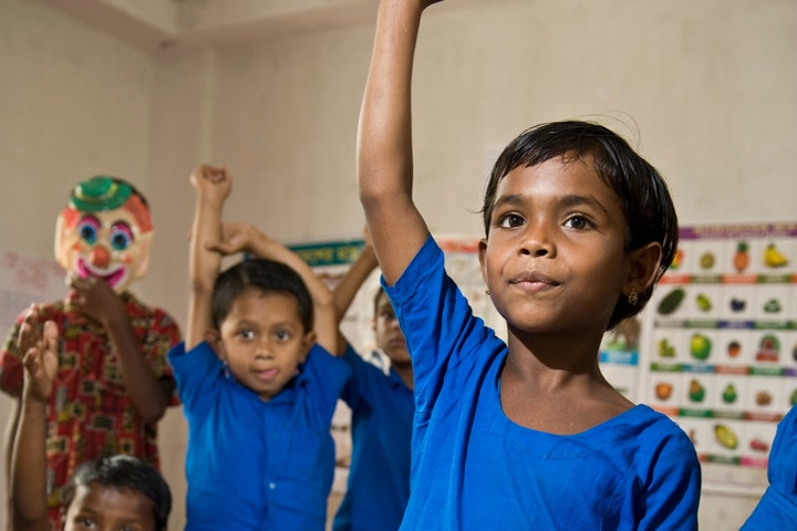 Child in Bangladesh raising their hand in school