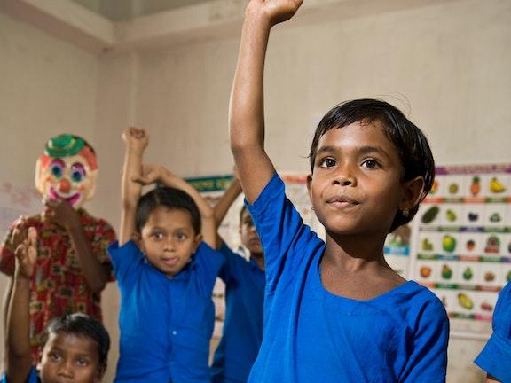 Child in Bangladesh raising their hand in school