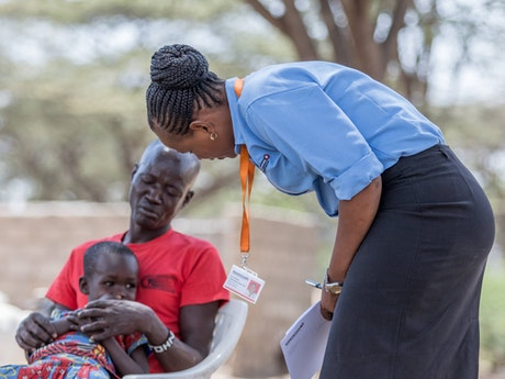 Jesca Edung Lomongin talking to a mother and her child in Turkana, Kenya