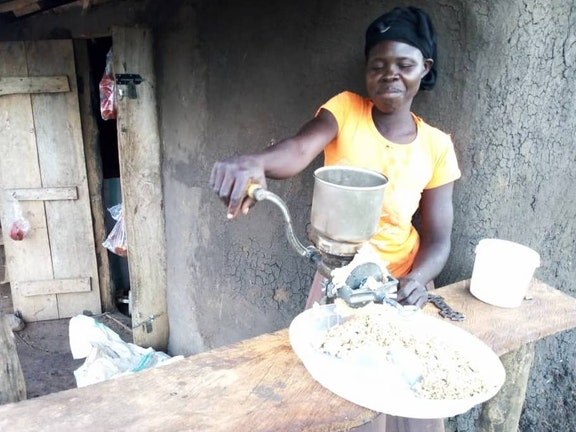 Esther demonstrates her groundnut grinding machine