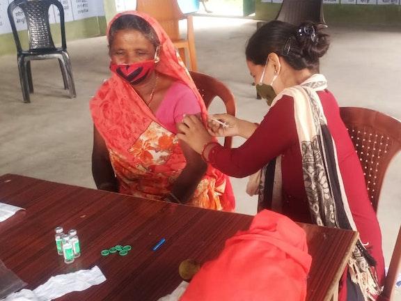 De 65-jarige Dulhari Devi wordt gevaccineerd door verloskundige Preeti Kumari. Dulhari komt uit een extreem arm gezin en werkt nog steeds in de nabijgelegen micamijnen. Eerst durfde zij zich niet te laten vaccineren, maar na de uitleg van de jongerenclub had ze er toch vertrouwen inn. Ze voelt zich nu veilig en beschermd.