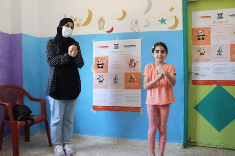 """The mother and the daughter are both participating in an activity on COVID-19 precaution techniques. (Project: """"Lebanon 2020: Supporting vulnerable boys, girls and caregivers, affected by the Beirut Blast"""", Mar Elias Camp in Beirut, May 2021, photography: Terre des Hommes Italy in Lebanon)."""