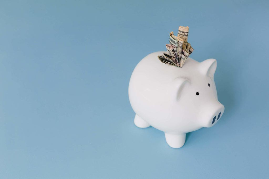 a blue background with a white piggy bank with bank notes jammed in the top