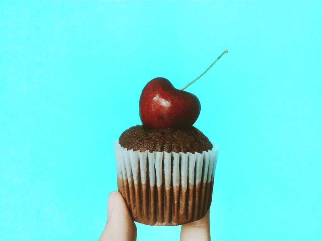 One product store - a hand holds a single cupcake with a cherry