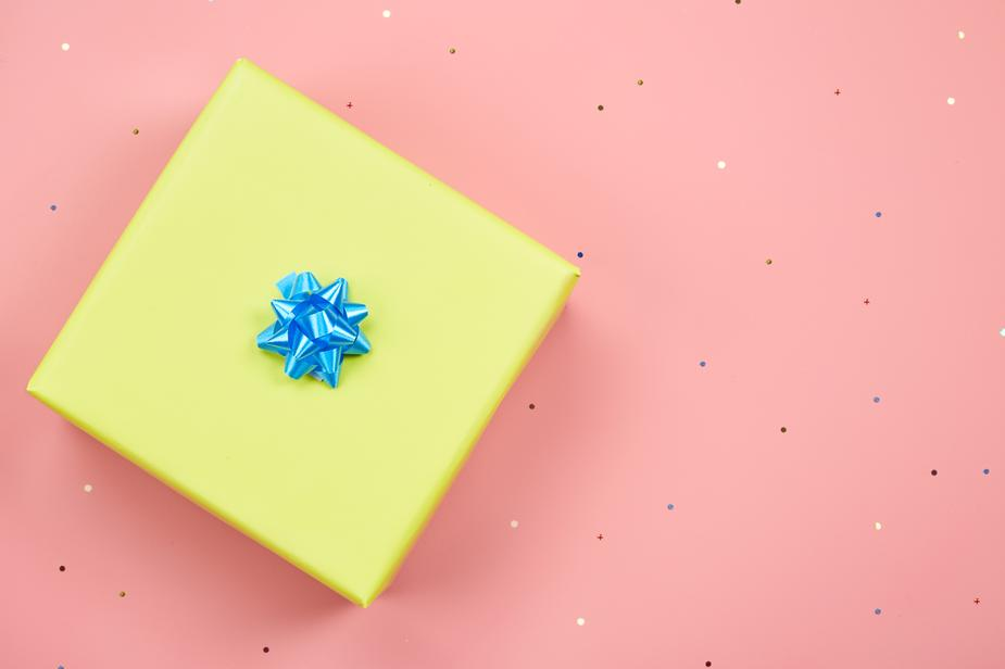 An overheard shot of a gift wrapped in yellow paper with a blue bow