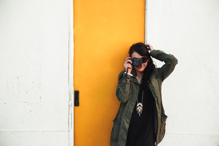Woman stands against a yellow door taking a photo
