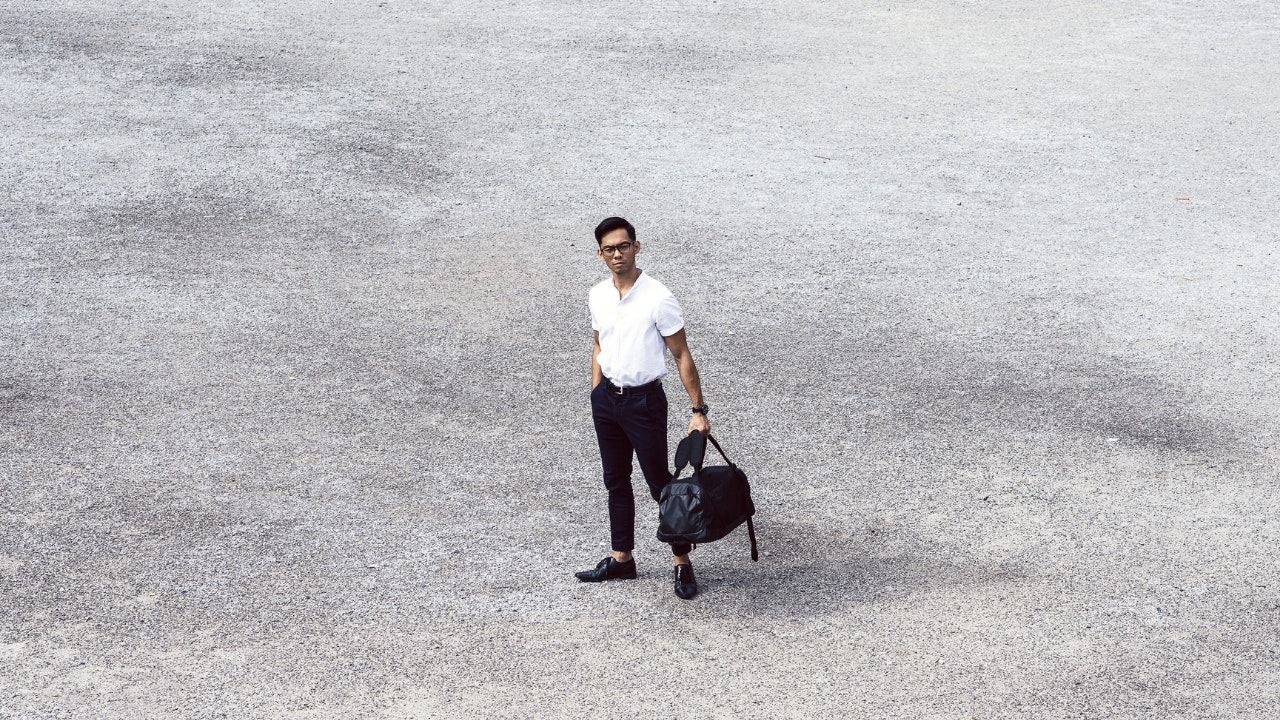 far shot of man holding bag