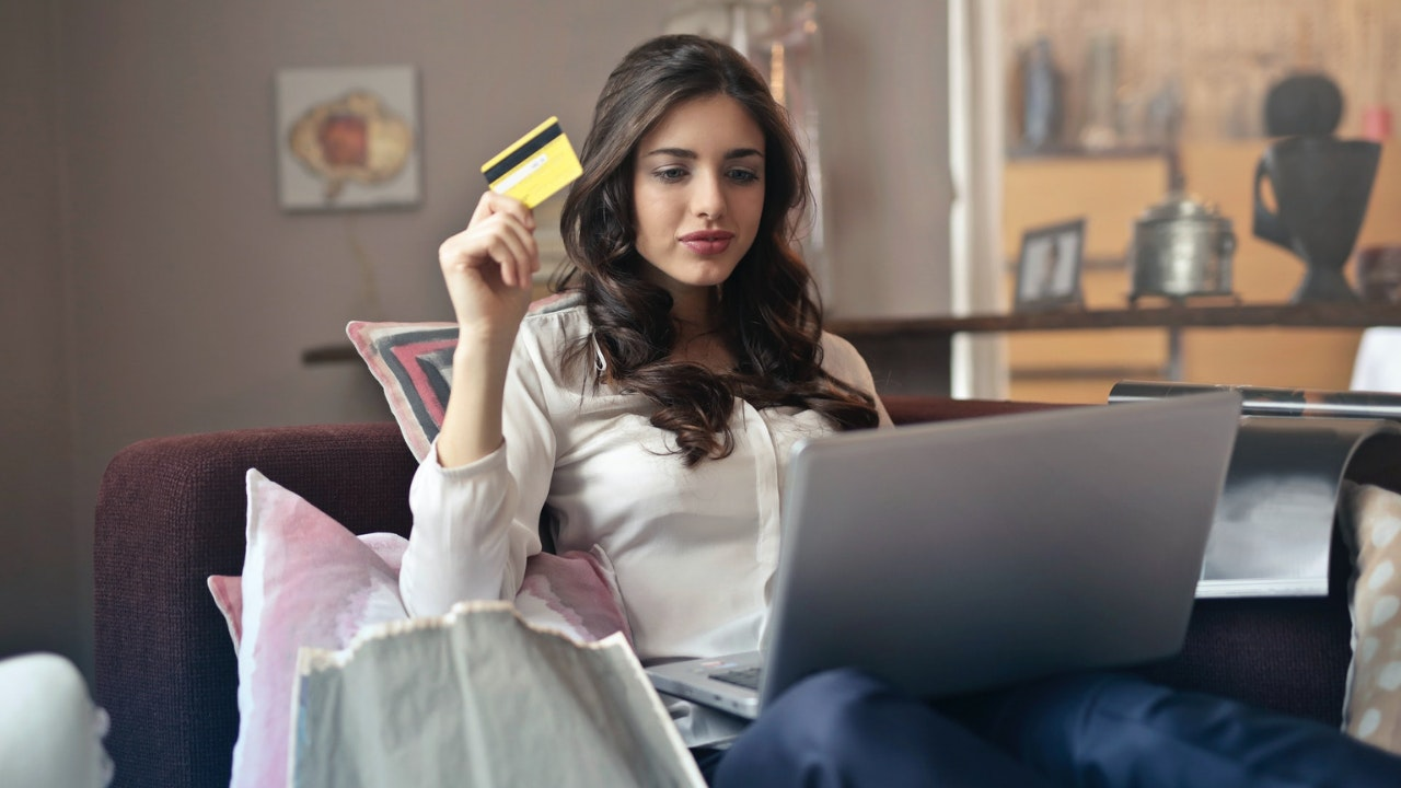 woman looking at a computer holding a credit card