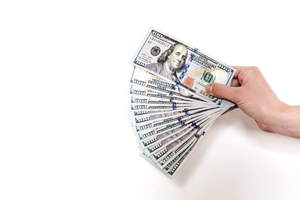 Hand mit Geldscheinen - Preispolitik